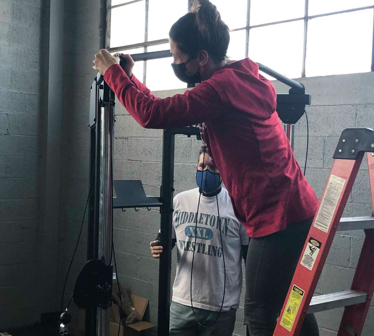 Samantha Aresco and Brandon Souto work on assembling equipment at the Overcomer Training Center on Sunday. Souto wrestled for OTC proprietor Mark Fong at Middletown High and spent time on MHS' coaching staff.