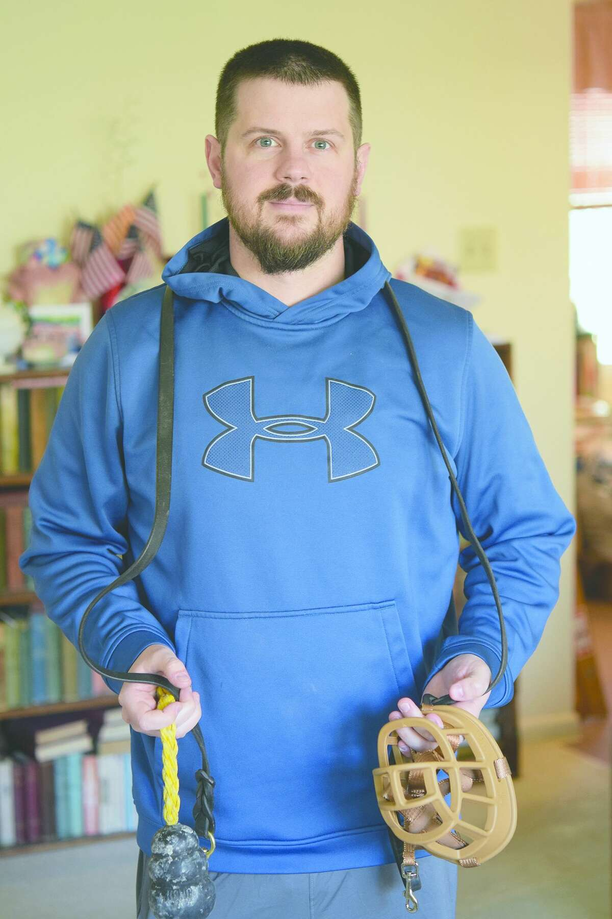 Billy Hollendonner, in the living room of his parents' home in Jacksonville, displays his dog handler tools of the trade.
