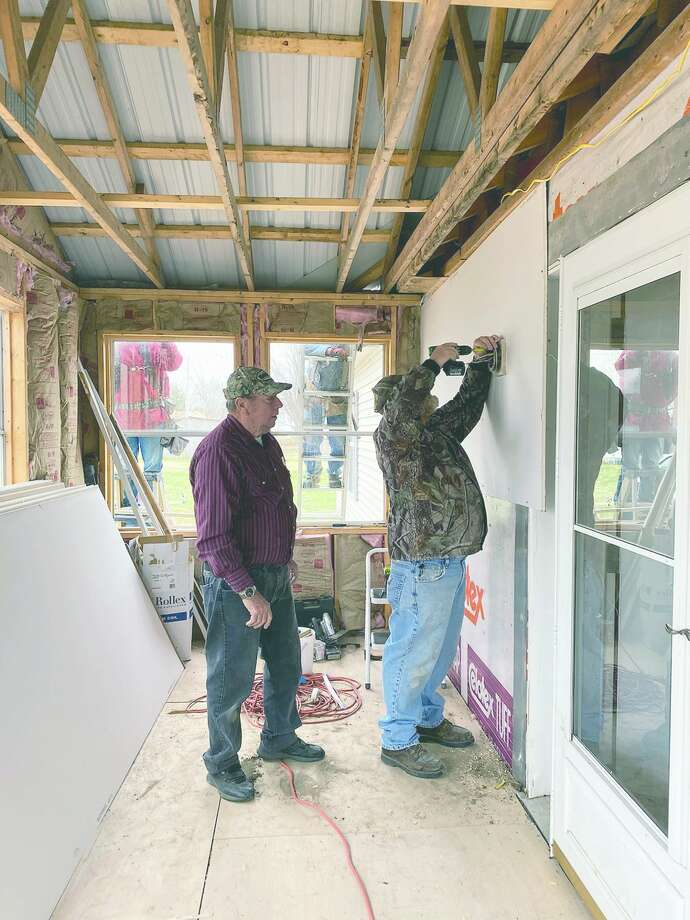 Junior Long and Ed Caskey work inside Janet Coonrod's home in Barrow. Several of the woman's neighbors joined forces this fall to get her into her new handicap-accessible home. Photo: Photo Provided