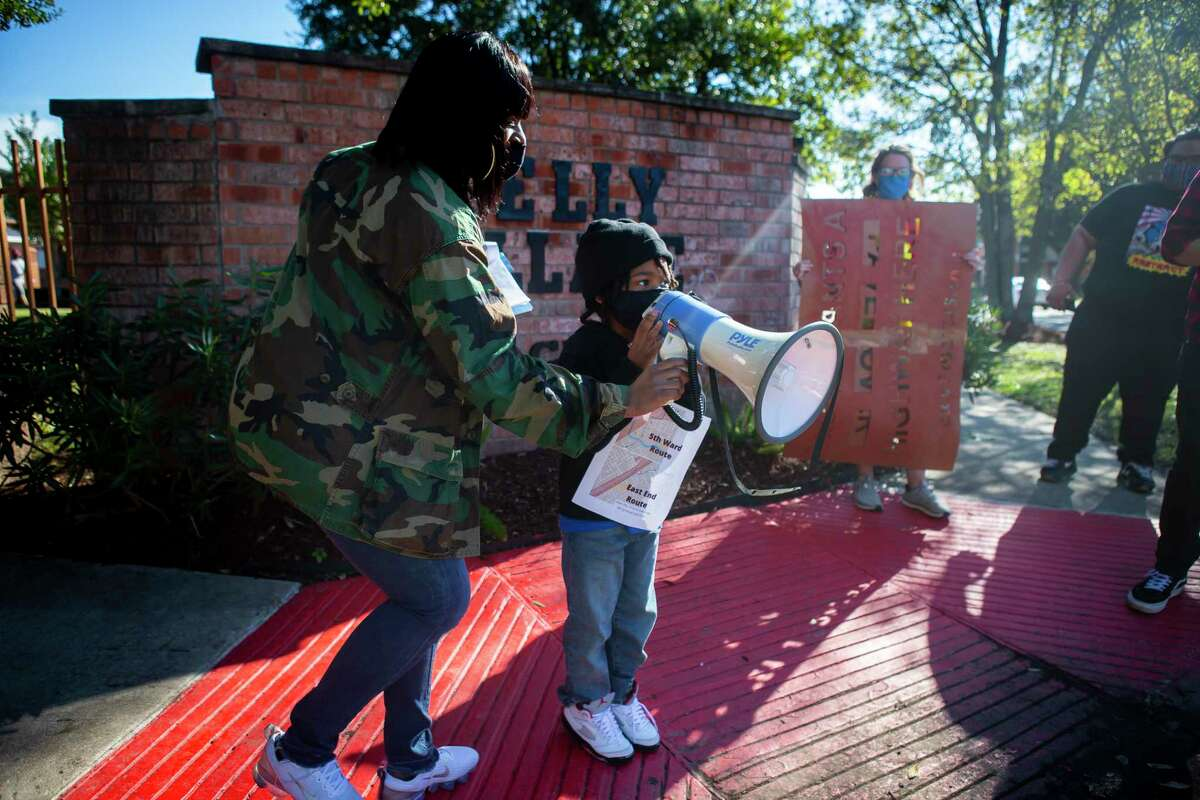 Kendra London helps her five year old son, Shahid, welcome participants to the Kelly Village apartments during a protest walk and rally opposing to the expansion of Interstate 45 in Fifth Ward on Dec. 6, 2020.