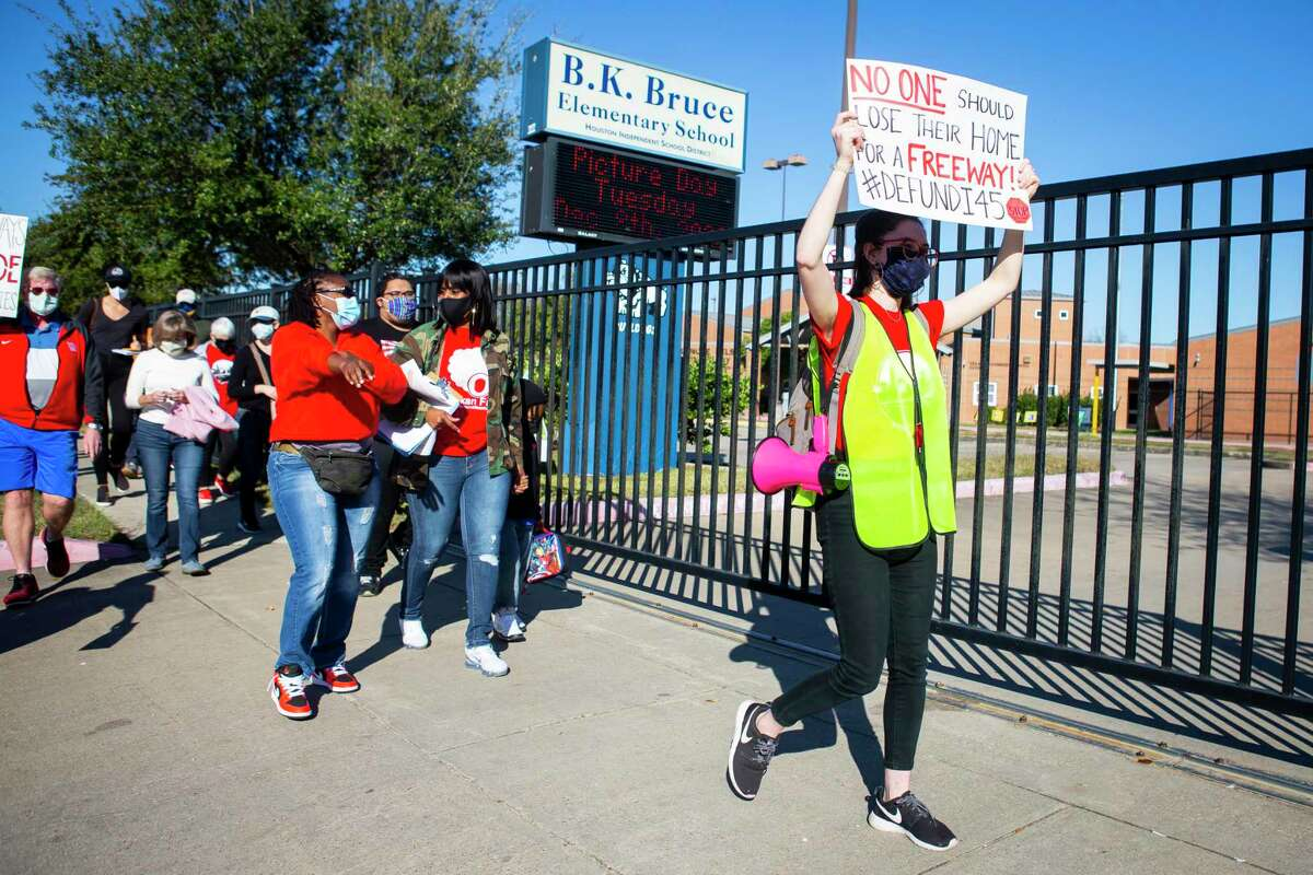 Chloe Cook, right, leads protestors by Bruce Elementary school during a protest walk in Fifth Ward on Dec. 6, 2020. Groups oppose the planned rebuild of Interstate 45 and the downtown freeway system.