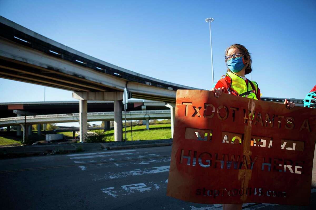 A participant carries a stencil sign during a protest walk of the expansion of Interstate 45 in Fifth Ward on Dec. 6, 2020.