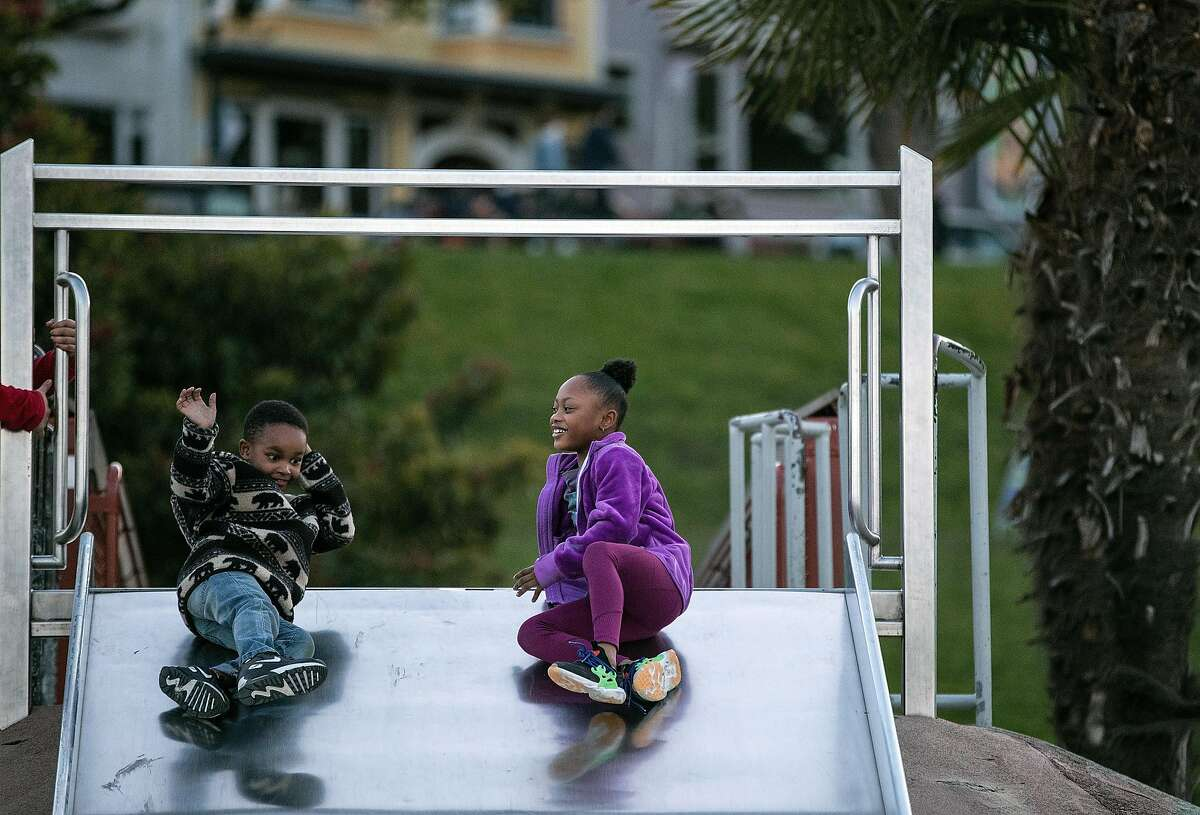 Cameron Hall, 5, and Bella Befford, 6, play on the slide at Mission Dolores Park playground in the Mission District where COVID-19 restrictions will be in effect later in the evening in San Francisco, Calif., on Sunday, December 6, 2020. Several Bay Area jurisdictions announced a COVID-19 lockdown ahead of statewide restrictions as ICU bed capacity has dropped in the region.
