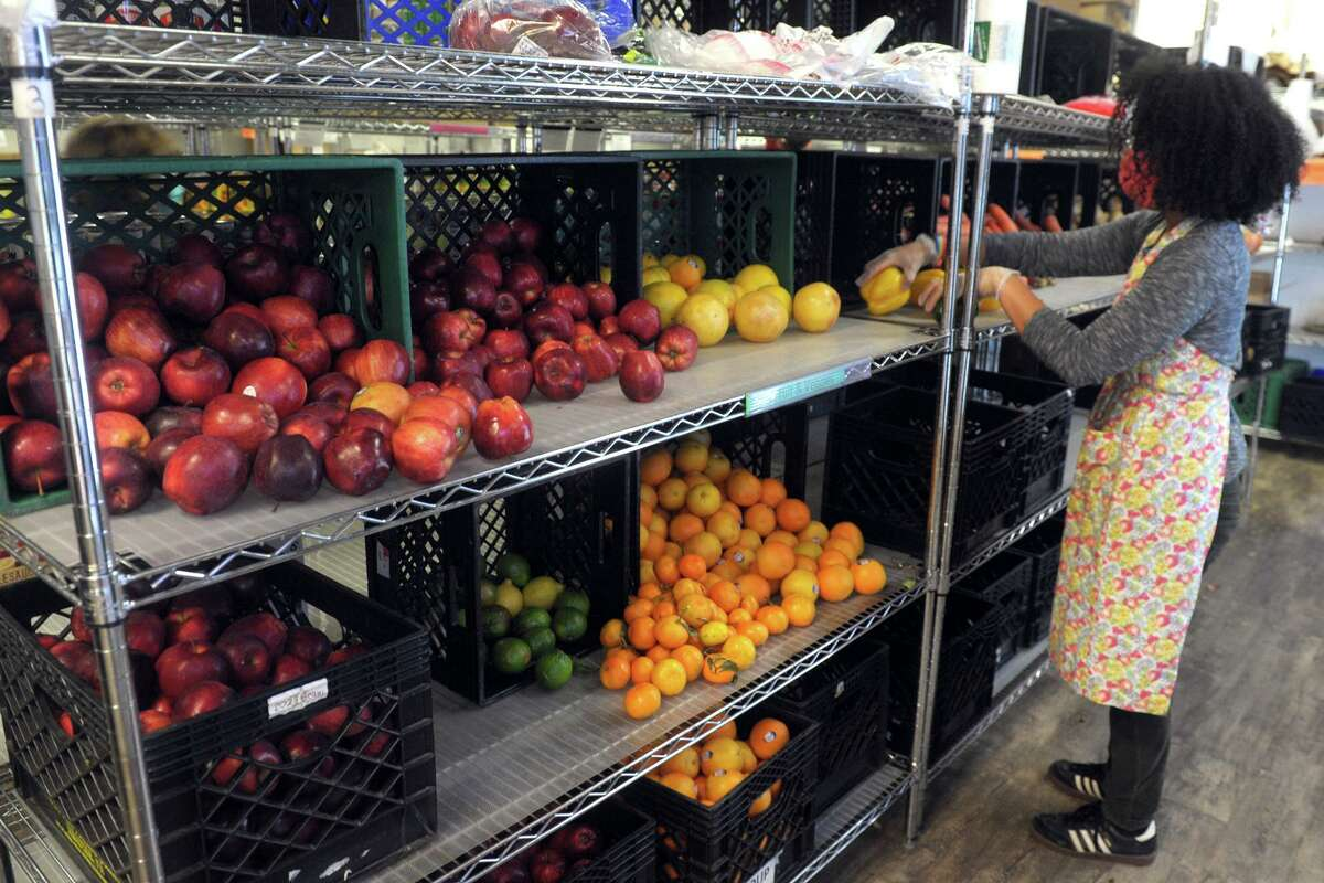 Volunteer Christina Randall stocks shelves with donated fresh fruit and vegetable at the Person-to-Person food pantry in Norwalk, Conn. Nov. 17, 2020.