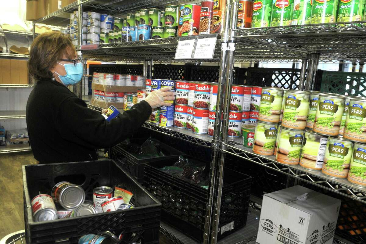 Volunteer Meryl Rhenfeld stocks the shelves with donated canned goods at the Person-to-Person food pantry in Norwalk, Conn. Nov. 17, 2020.