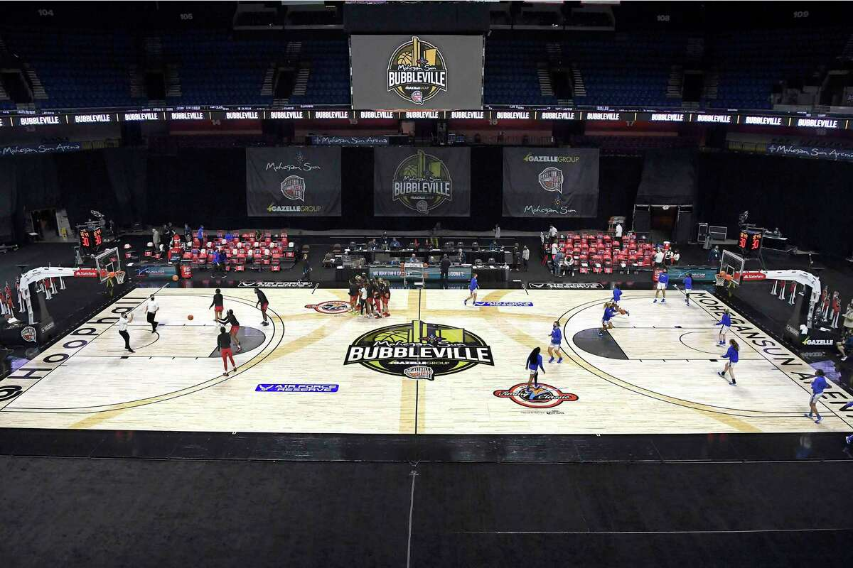 """The NCAA's """"Bubbleville"""" logo in December 2020 at Mohegan Sun Arena in Uncasville, Conn. Mohegan Sun revenue dropped 31 percent in the year of COVID-19, besting the results for smaller Mohegan Gaming & Entertainment casinos in Pennsylvania and Ontario, Canada. (AP Photo/Jessica Hill)"""