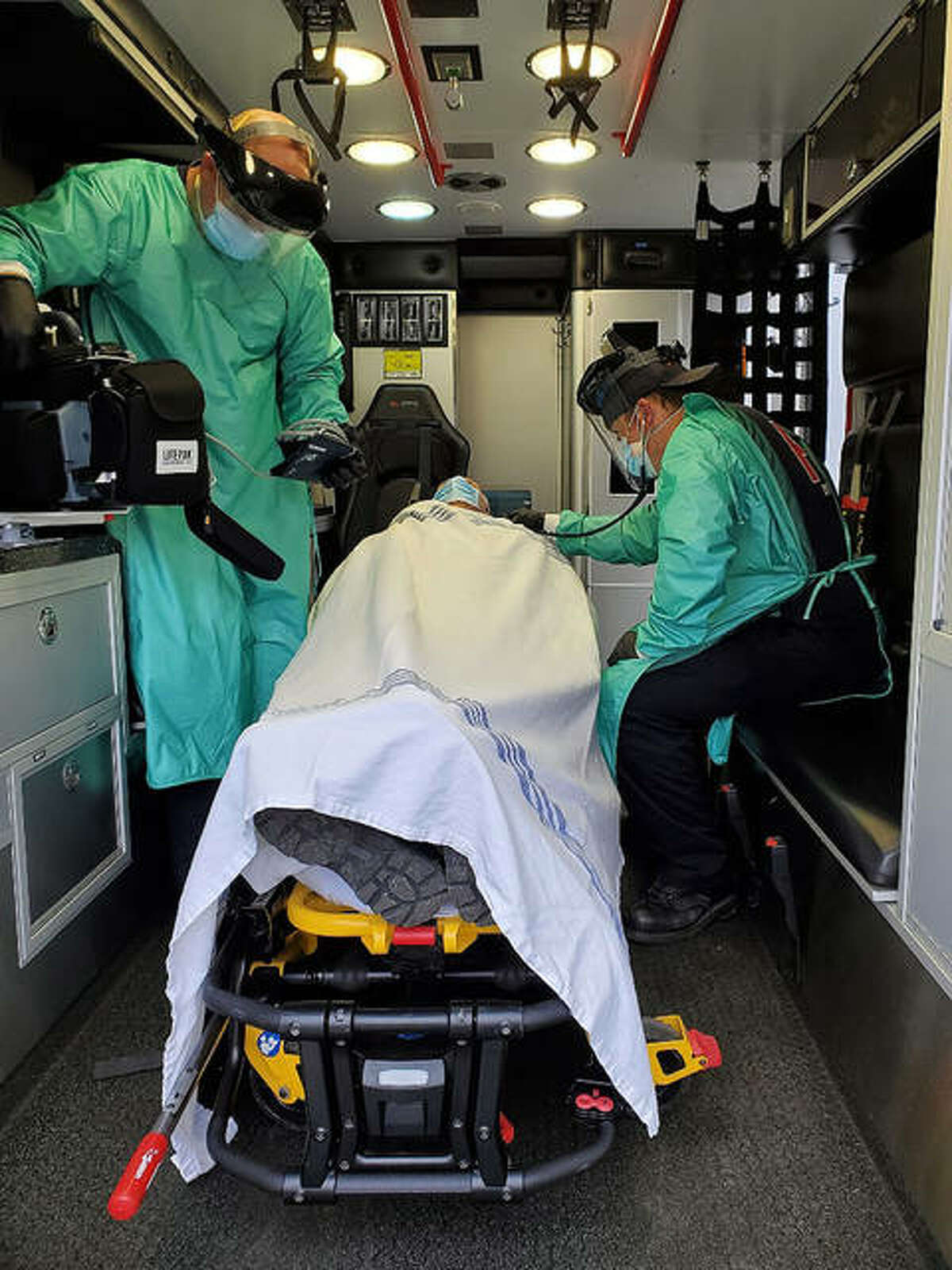 Members of the Edwardsville Fire Department and its EMS crews demonstrate Thursday what they have been wearing during calls while tending to suspected or known coronavirus patients.