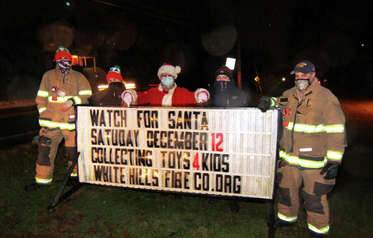 Santa, center, poses with firefighters Jon Bednarz, left, Stephanie Tatun and Lt. Daniel Tatun and Jim Norkus, right, during the White Hills Fire House annual tree lighting in Shelton, Conn., on Saturday Dec. 5, 2020.