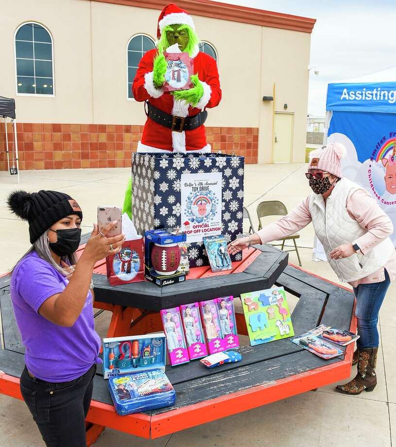 Smiles From Heaven Vice President Betsy Sanchez, President Ray Sanchez, dressed as The Grinch, and Board-member Norma Helzer go live on social media encouraging the community to drop off toys for Bella's 4th Annual Toy Drive, Saturday, Dec. 5, 2020, at Harley Davidson of Laredo. Photo: Danny Zaragoza, Staff Photographer / Laredo Morning Times