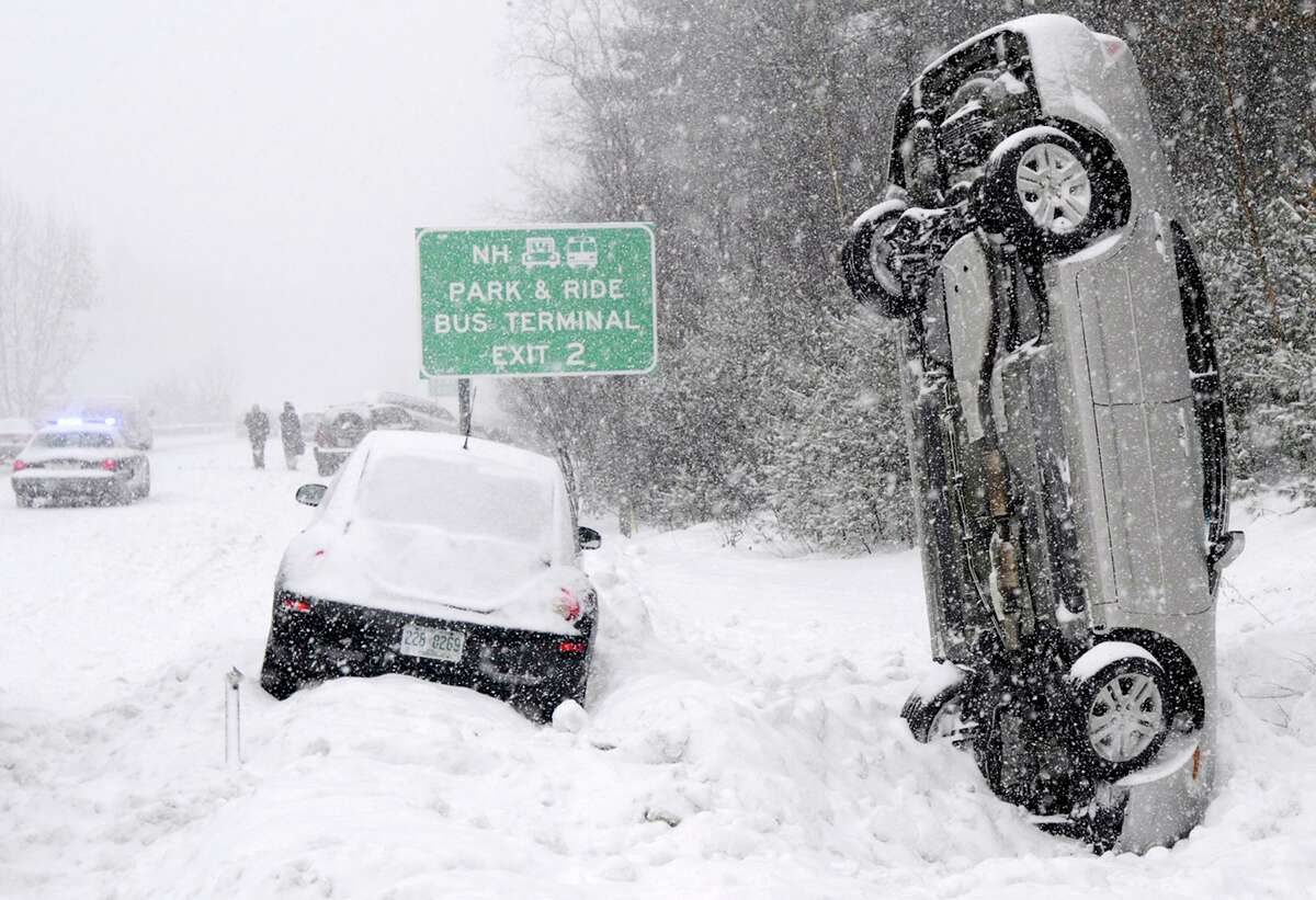 This file photo shows a car that landed vertically into a snowbank after a multiple vehicle accident on Interstate 93 during a snow storm north of Salem, N.H. No one was injured.