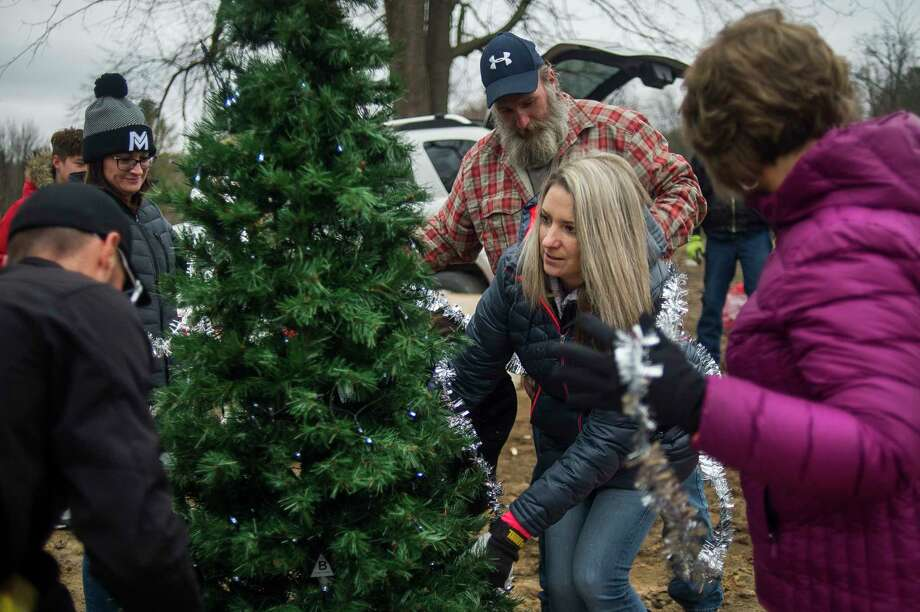 Family members of Crystal Kerns, second from right, gather Sunday afternoon to decorate a Christmas tree where her home once stood in downtown Sanford, before it was destroyed by the dam failures and flood in May. For more photos, visit www.ourmidland.com. (Katy Kildee/kkildee@mdn.net)