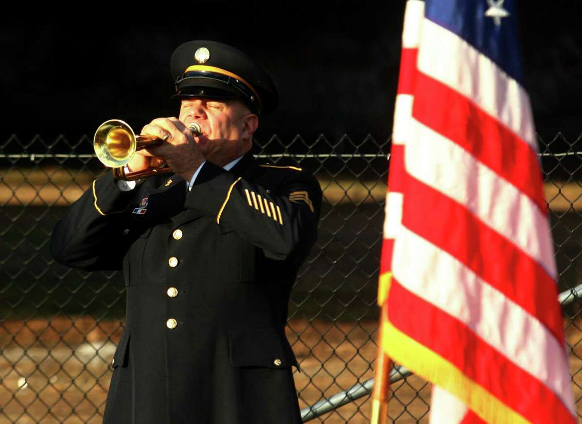 File photo of Staff Sgt. Chris Schrock, with the 102nd Army Band in Rockville, plays taps during the Pearl Harbor Memorial Park Dedication Ceremony on East Street in New Haven, Conn., on Thursday Dec. 6, 2018.