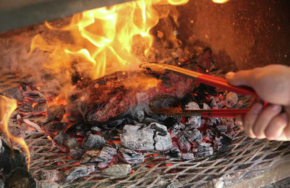 Flames ignite as a cut of tri-tip meat gets placed on top of hot coals by Bandit BBQ owner and pitmaster Brandon Peterson.