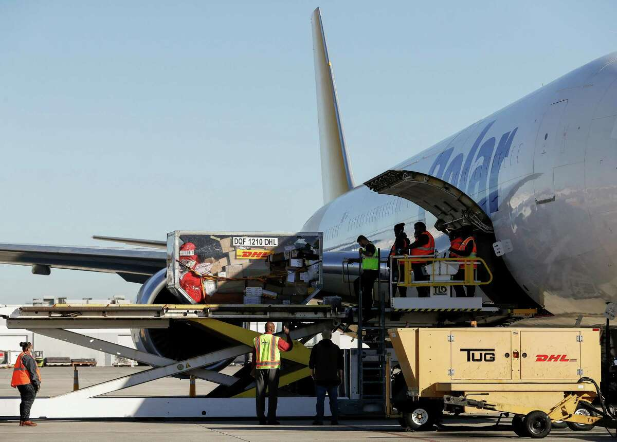 DHL ground handlers work to unload packages that arrived in an airplane Tuesday, Nov. 17, 2020, in Houston. Major couriers are preparing for an unprecedented surge in demand for holiday shipping due to the pandemic.