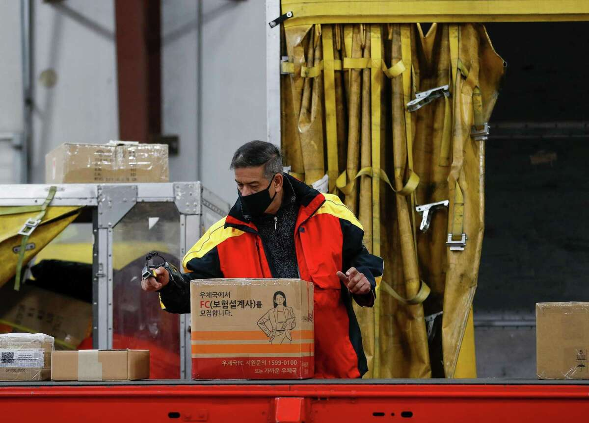 DHL driver Ranier Castillo scans packages at the sorting line Tuesday, Nov. 17, 2020, in Houston. Major couriers are preparing for an unprecedented surge in demand for holiday shipping due to the pandemic.