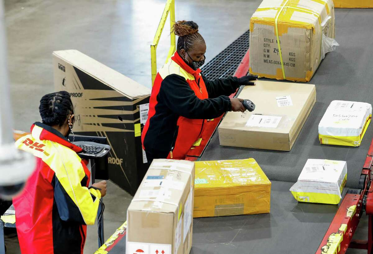 DHL drivers Whitney Duncan, left, and Sandra Moore scan packages at the sorting line Tuesday, Nov. 17, 2020, in Houston. Major couriers are preparing for an unprecedented surge in demand for holiday shipping due to the pandemic.
