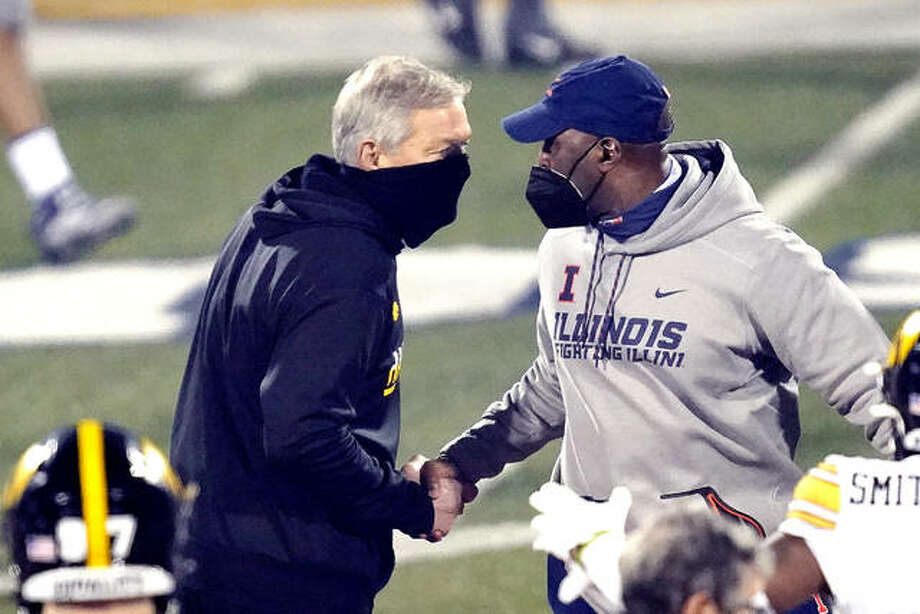 Iowa head coach Kirk Ferentz, left, and Illinois head coach Lovie Smith shake hands after Saturday's game at memorial Stadium in Champaign. Iowa won 35-21. The Illini will play at No. 15 Northwestern at 11 a.m. Saturday in the Land of Lincoln Trophy game. Photo: Associated Press