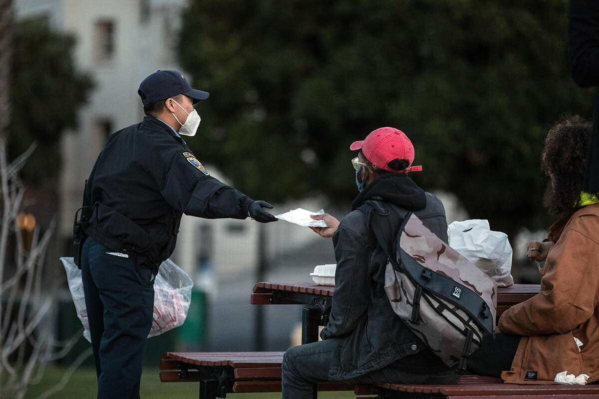 A SFPD cadet hands out masks to guests at Dolores Park in the Mission District where COVID-19 restrictions will be in effect later in the evening in San Francisco, Calif., on Sunday, December 6, 2020. Several Bay Area jurisdictions announced a COVID-19 lockdown ahead of statewide restrictions as ICU bed capacity has dropped in the region.