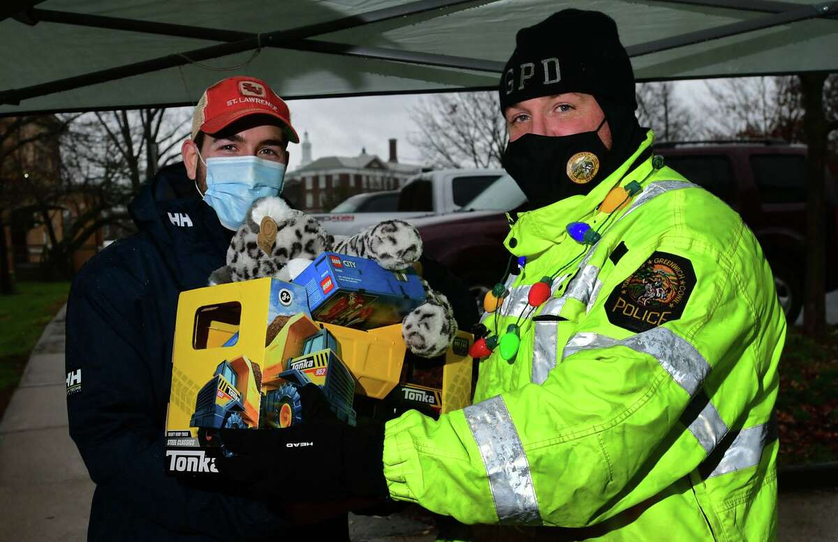 Resident Nathan Long donates toys to officer Thomas Huestis as The Greenwich Police Department hold their toy drive Saturday, December 5, 2020, to help needy families at the public safety complex in Greenwich, Conn.
