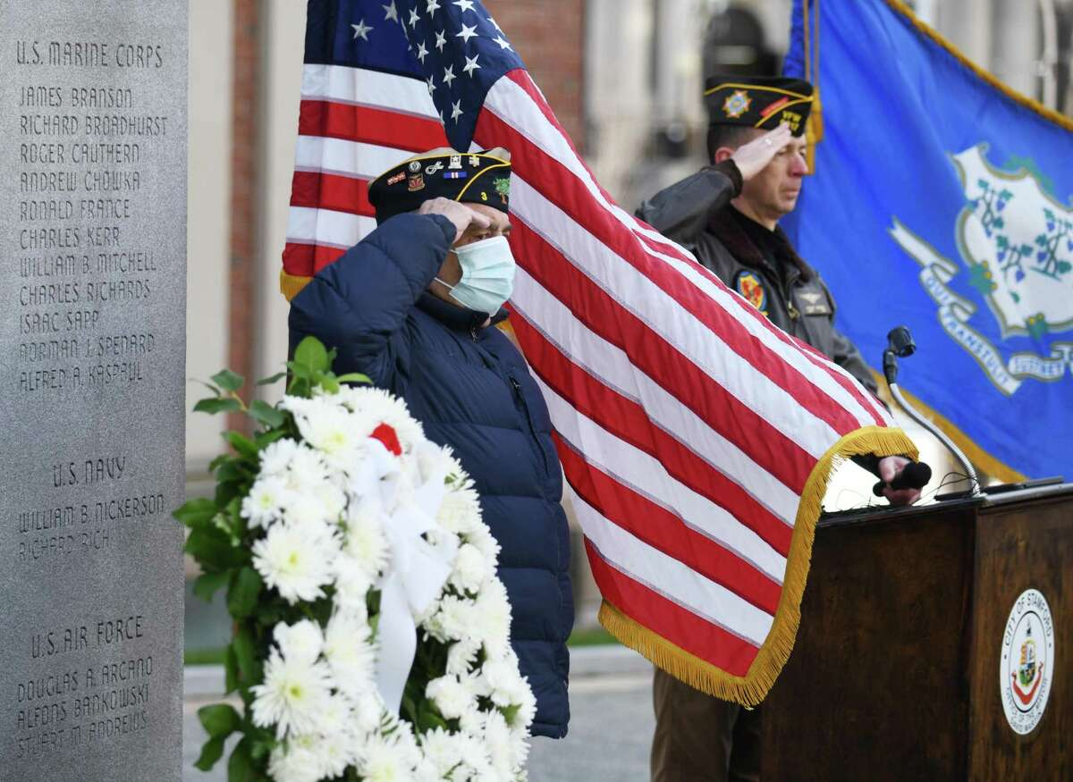 U.S. Army veteran Grey Watson, left, and U.S. Navy Capt. (Ret.) Alan Gerard salute during the Pearl Harbor Day ceremony at Veterans Park in Stamford, Conn. Monday, Dec. 7, 2020. The ceremony recognized those who served and paid respect to those who lost their lives in the 1941 attack on Pearl Harbor.
