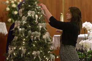 One of 26 silver angle wings being hung on a tree at the altar of St. Rose of Lima, in Newtown, Conn., at the start of a special mass on Thursday, December 14, 2017. The service was held on the fifth anniversary of the day 20 first-graders and six educators were killed at Sandy Hook Elementary School.