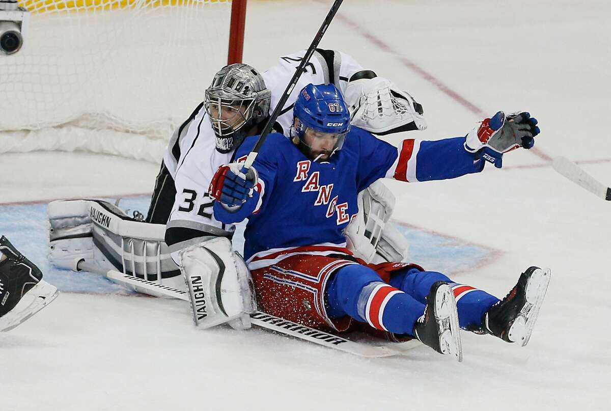 """Professional hockey player Benoit Pouliot of the New York Rangers collides with Jonathan Quick of the Los Angeles Kings in a game in 2014. Intentional collisions are prohibited in amateur, """"no-check"""" leagues."""