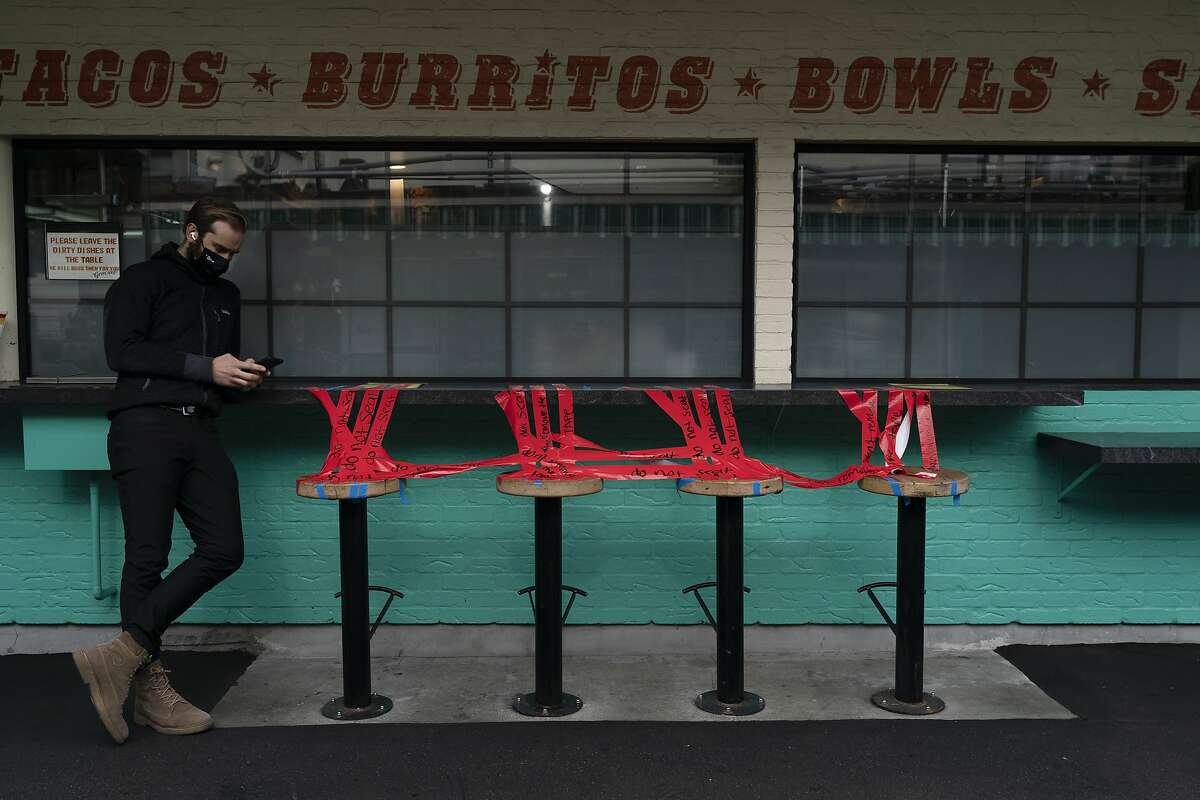 Stools are taped off at a restaurant in Los Angeles, where a stay-at-home order went into effect Monday.