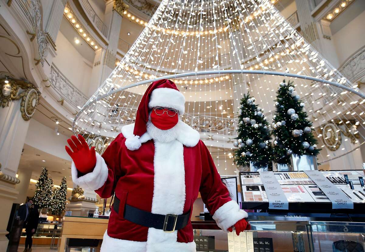 Santa Claus, or Christopher MacGowan in real life, greets customers arriving at Neiman Marcus in San Francisco. Christmas shopping is a bit muted in 2020.