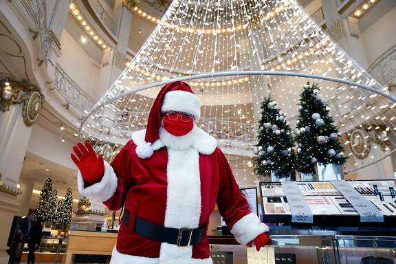 Santa Claus, Christopher MacGowan in real life, greets customers arriving to shop at Neiman Marcus in San Francisco, Calif. on Saturday, Dec. 5, 2020.
