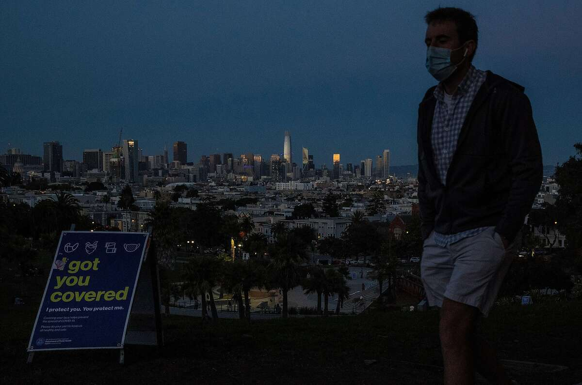A pedestrian walks by the top of Mission Dolores Park in the Mission District where COVID-19 restrictions will be in effect later in the evening in San Francisco, Calif., on Sunday, December 6, 2020. Several Bay Area jurisdictions announced a COVID-19 lockdown ahead of statewide restrictions as ICU bed capacity has dropped in the region.