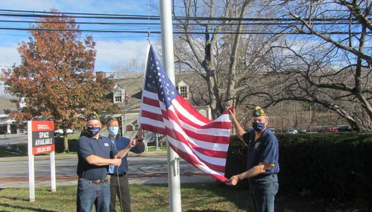 Raising the new flag in front of the gazebo on Nov. 27 in Wilton Center on are, from left, Jeff Turner, past Kiwanis Club president Kiwanis and American Legion member, Greg Chann, Kiwanis president and Legion member, and Bill Glass, Commander American Legion Post 86. The flag honors George McKendry, a founding member and early president of the Kiwanis Club.
