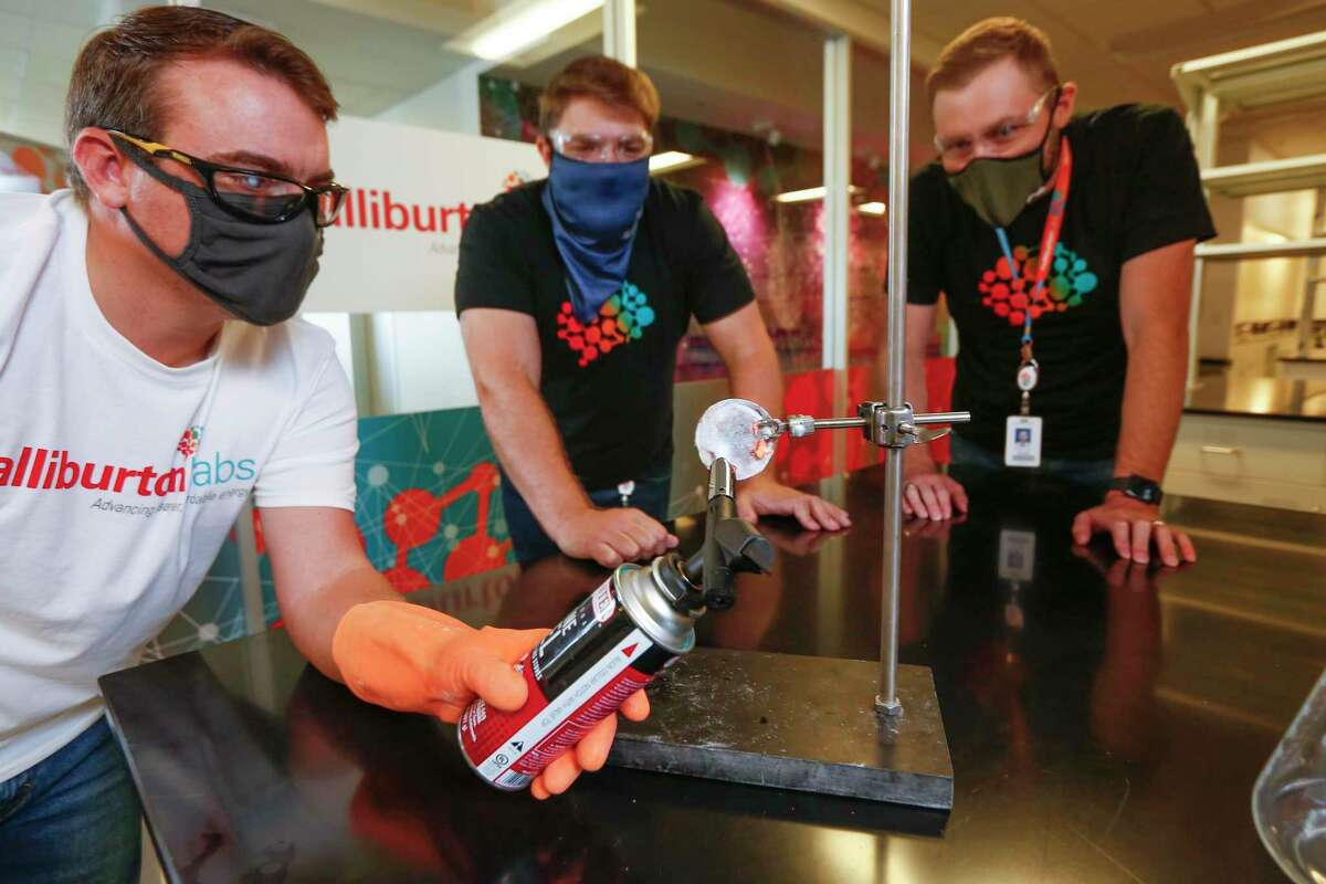 NanoTech COO John Jarvis (l-r) demostrates how fire resistant a Nano Shield Forge is NanoTech as CEO Mike Francis and Halliburton Labs Executive Director Scott Gale at Halliburton's new clean energy tech lab observe Friday, Aug. 21, 2020, in Houston.