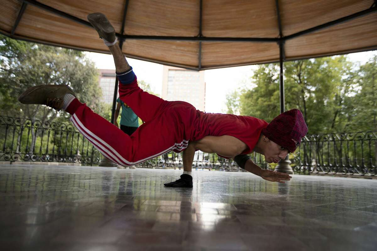 FILE - In this Tuesday, Aug. 18, 2020 file photo, Carlos Cruz, a breakdancer, practices at a kiosk in Alameda park after being closed off to the public for nearly five months due to the new coronavirus pandemic, in Mexico City. Breakdancing has been confirmed as an official Olympic sport. The International Olympic Committee's pursuit of urban events to lure a younger audience saw street dance battles officially added to the medal events program at the 2024 Paris Games. (AP Photo/Fernando Llano, File)