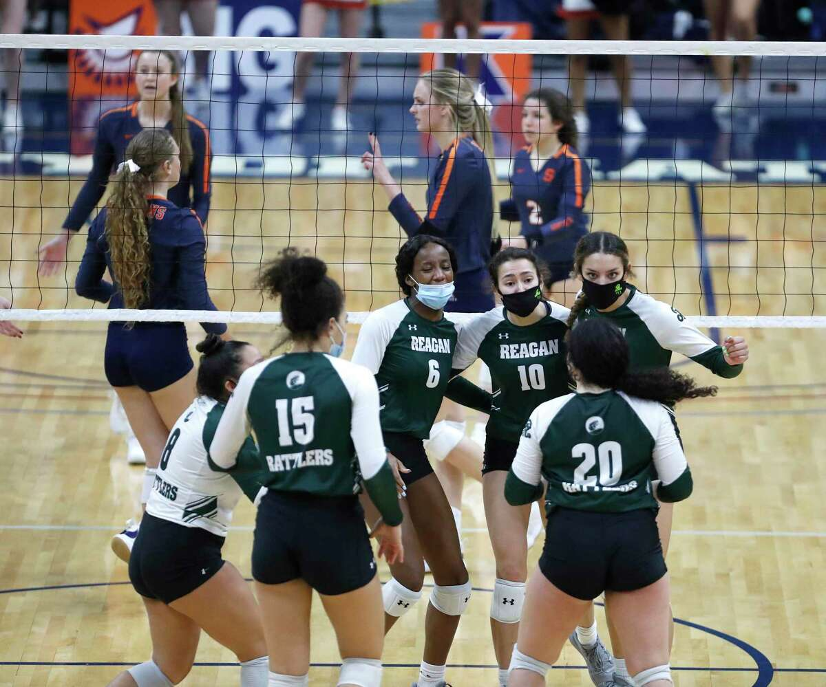 Reagan teammates celebrate a point scored against Seven Lakes during a state semifinal volleyball game at The Merrell Center, Monday, December 7, 2020, in Katy.