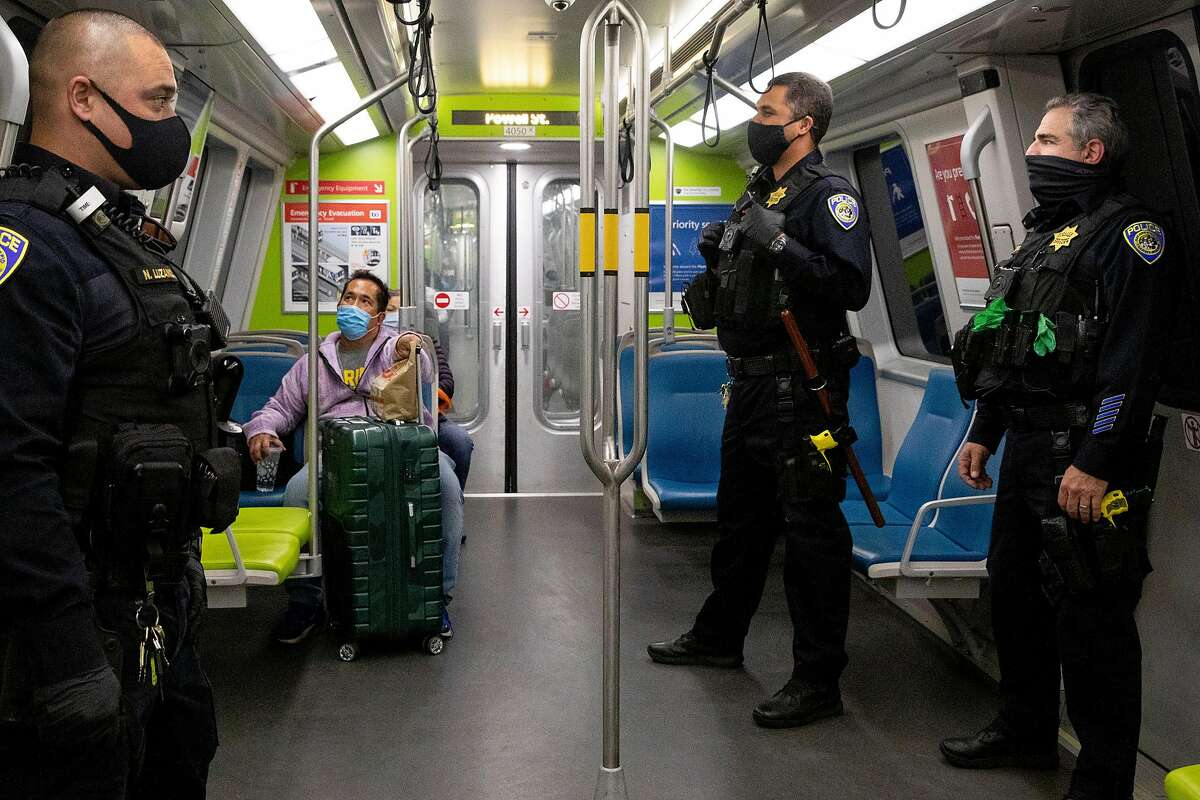 (From left) BART police officers Nick Luzano, Eric Kelly and Eric Hofstein wear masks while patrolling a Richmond bound train from Powell Street Station BART platform in San Francisco, Calif. Friday, November 20, 2020. As overdoses have skyrocketed in San Francisco during the pandemic, there are questions if the same has happened on BART, long-plagued by drug use on the trains, but which has seen a dramatic drop in ridership since shelter-in-place.