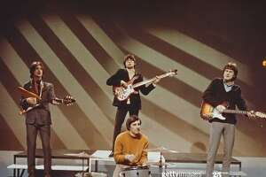 English rock group The Kinks, from left, Dave Davies (playing a Gibson Flying V guitar), Pete Quaife (behind, playing Rickenbacker bass guitar), Mick Avory and Ray Davies, perform on a television show at BBC Television Centre in London in December 1965. (Photo by David Redfern/Redferns)