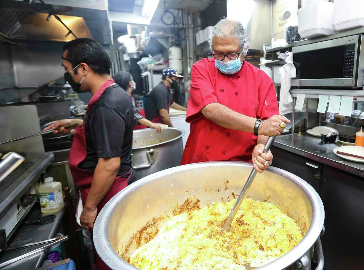 Himalaya Restaurant chef and owner Kaiser Lashkari stirs up a dish in the kitchen at his Houston restaurant on Wednesday, Nov. 18, 2020. During the pandemic, Lashkari noticed his blood sugar was spiking, so he began walking, cutting carbs from his diet and now he's lost about 40 pounds.