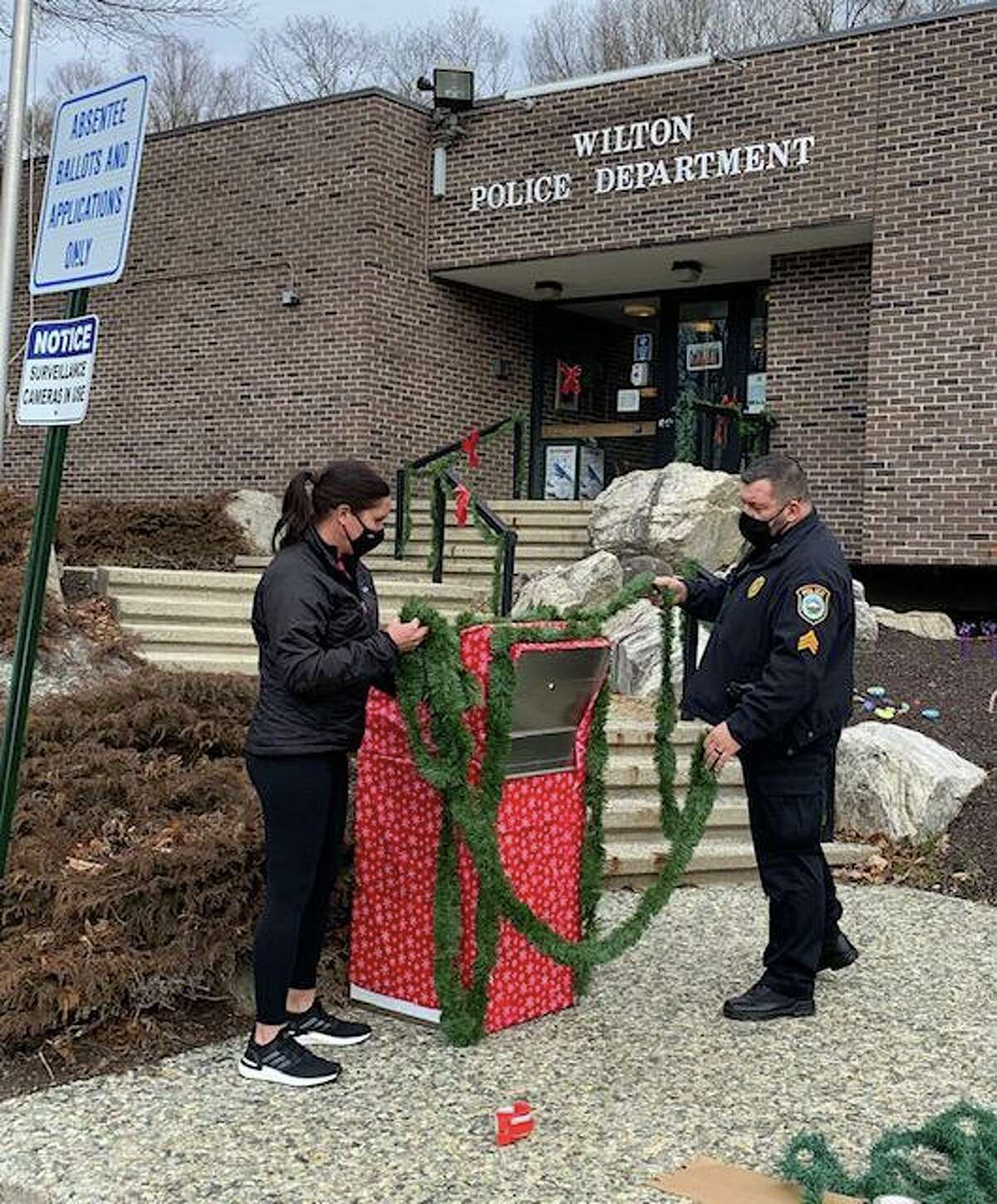 Wilton Social Services Director Sarah Heath and Sgt. Anthony Cocco of the Wilton Police Department, decorate the ballot box, ready for its new role as Santa's Mailbox.