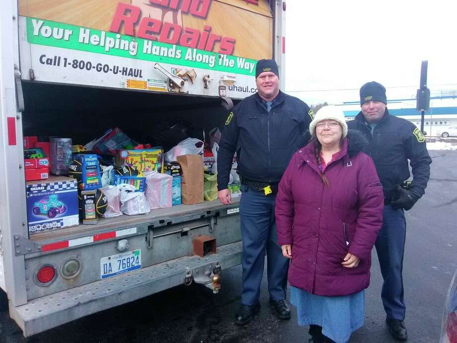 MSP troopers David Skorka and Chris Ingalls present a truck loaded with items collected during the 2019 Stuff a Blue Goose event. Items are being donated to Lisa Clarke of ECHO His Love. (Courtesy photo)