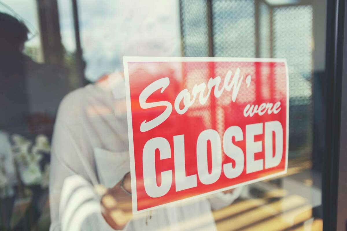 A store owner is pictured putting up a closed sign in the window. (Photo courtesy of Getty Images)