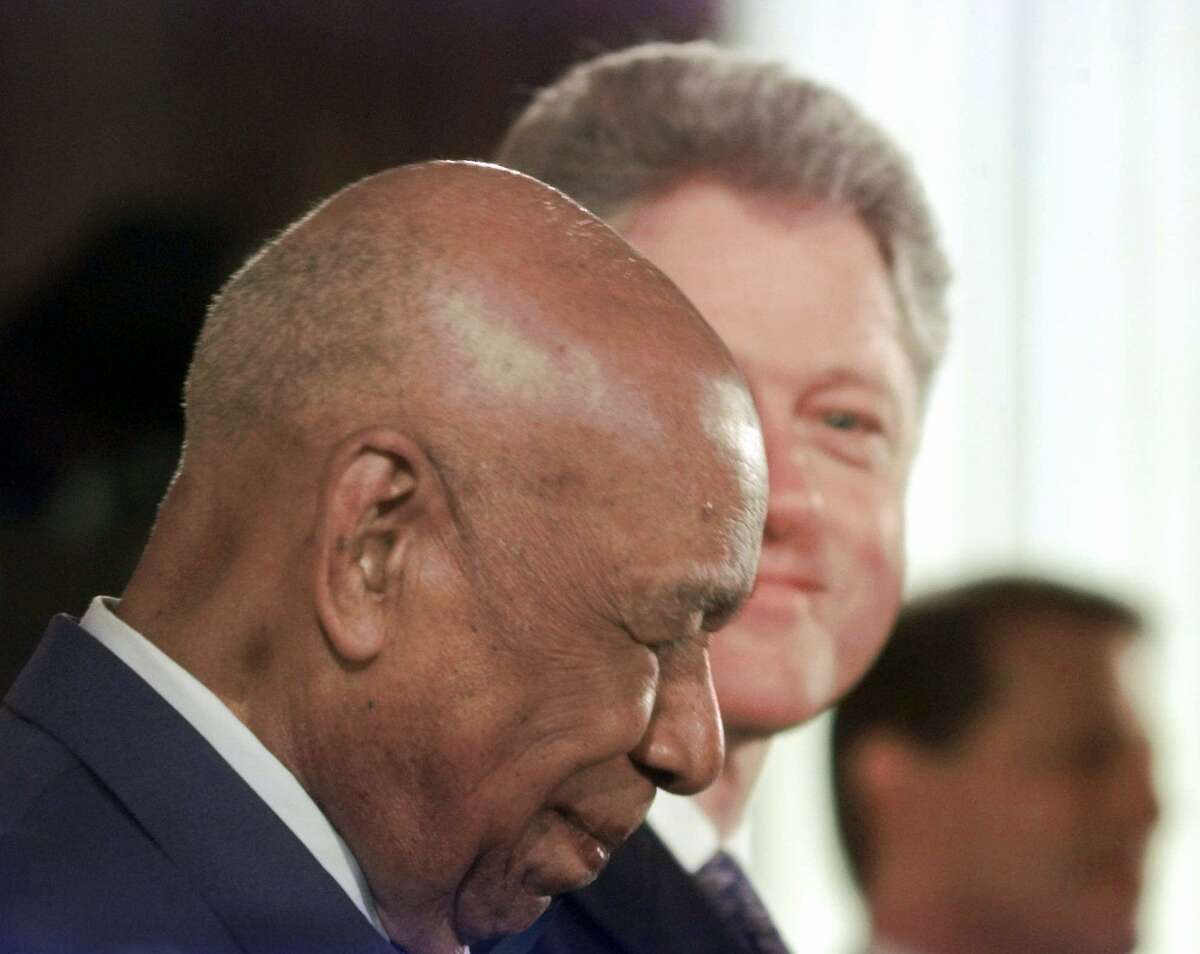 Herman Shaw, a Tuskegee Syphilis Study victim, receives an official apology from President Bill Clinton in 1997. That shameful study is among the reasons for Black people's trepidations about a COVID vaccine.