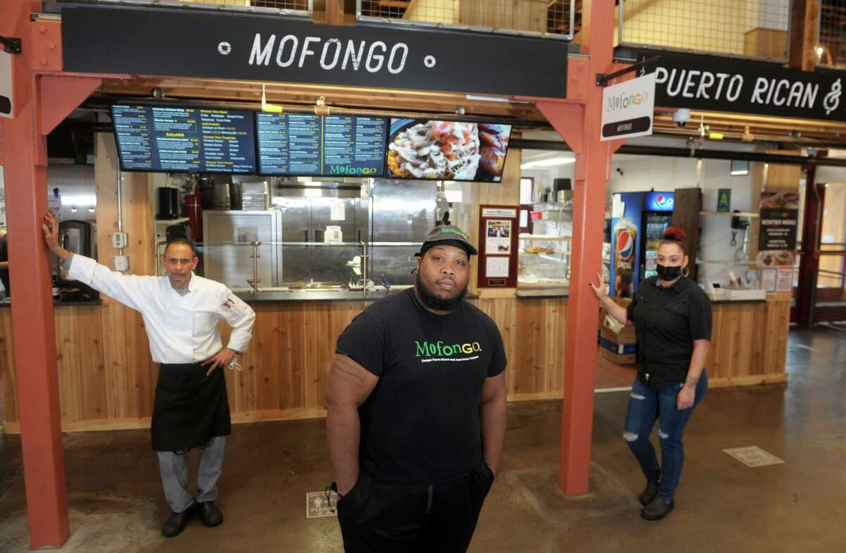 Claude Mann poses with Chef Raymond Rodriquez and general manager Cassandra Nieves in front of MofonGo Restaurant, inside the Parkville Market, in Hartford, Conn. Dec. 8, 2020.
