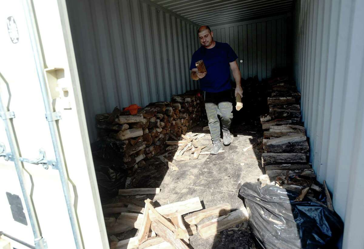 Jake Mazzu chops wood for the grillers in a backyard trailer as a line wraps around the building at the Friday opening of 1701 Barbecue in Beaumont, which had its grand opening Tuesday. Photo taken Friday, December 4, 2020 Kim Brent/The Enterprise