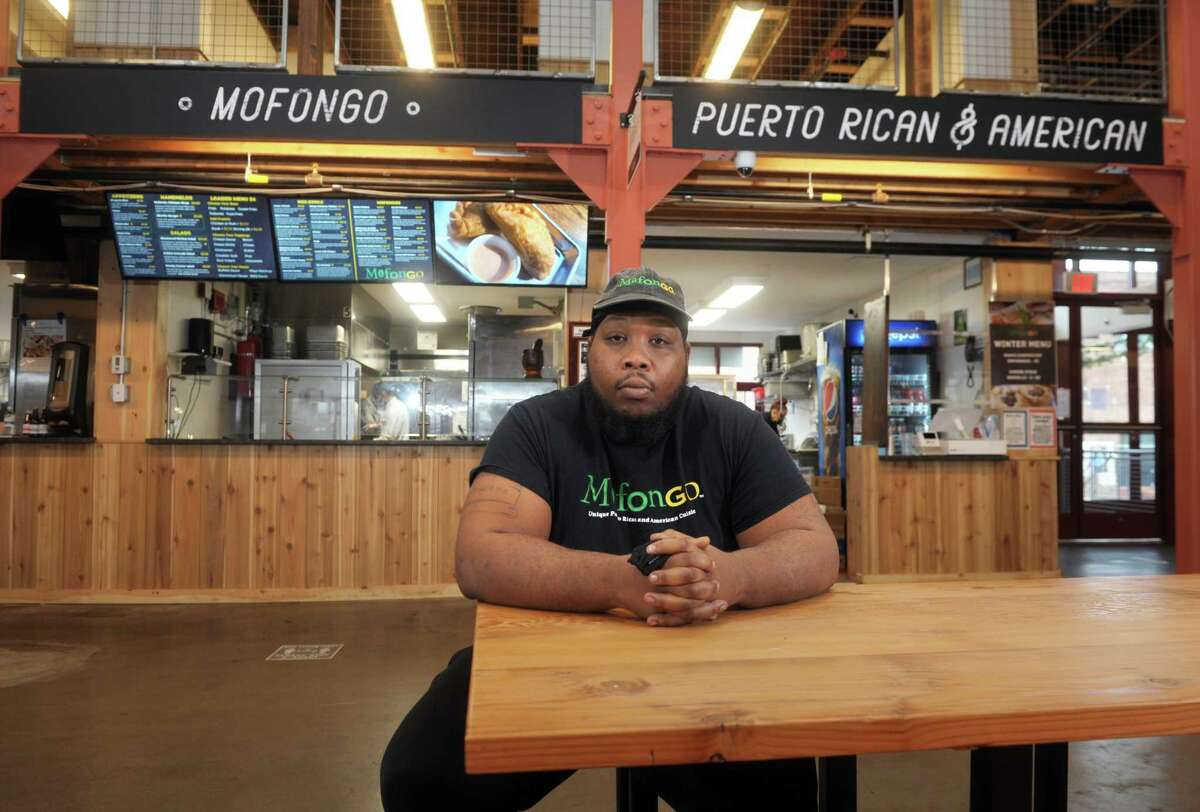 Claude Mann poses in front of MofonGo Restaurant, inside the Parkville Market in Hartford, Conn. Dec. 8, 2020.