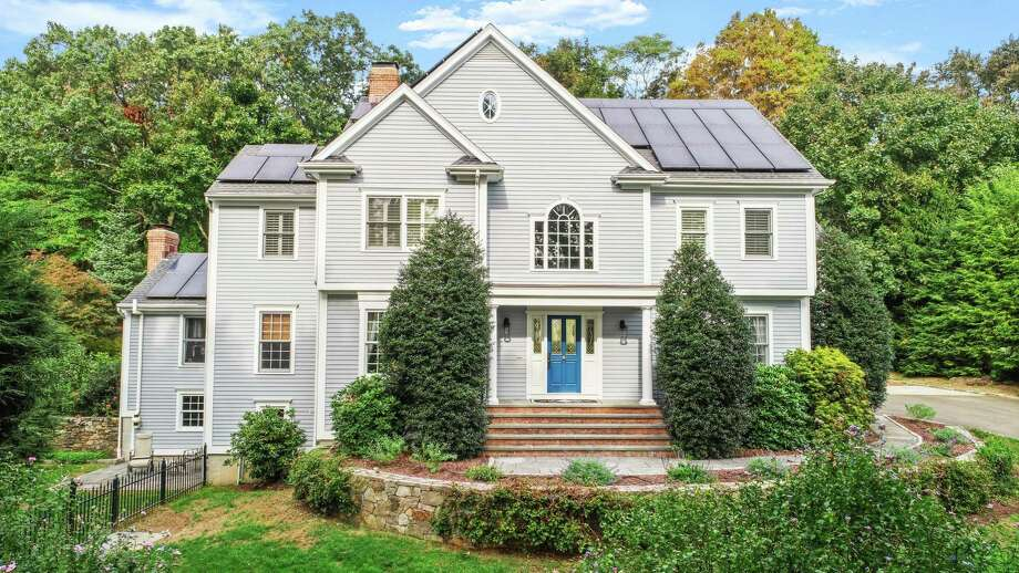 """The gray colonial house at 233 High Meadow Road in Southport active has solar panels. What sits under those panels also contribute to the modern day living and entertaining standards of today's homeowners. """"This property really has everything today's buyers are looking for,"""" said Marketing Broker Julie Vanderblue, of The Vanderblue Team and Higgins Group Real Estate. """"A classic well-built colonial with a fabulous open floor plan, home offices - which are in high demand, a walk-out lower level offering so many options, and amazing grounds with an in-ground pool and spa. Add to that the convenient and sought after Southport location and you have the perfect package."""" Photo: Contributed Photo /"""