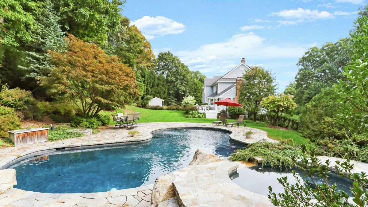 The Gunite in-ground swimming pool features a spa that cascades into the pool.