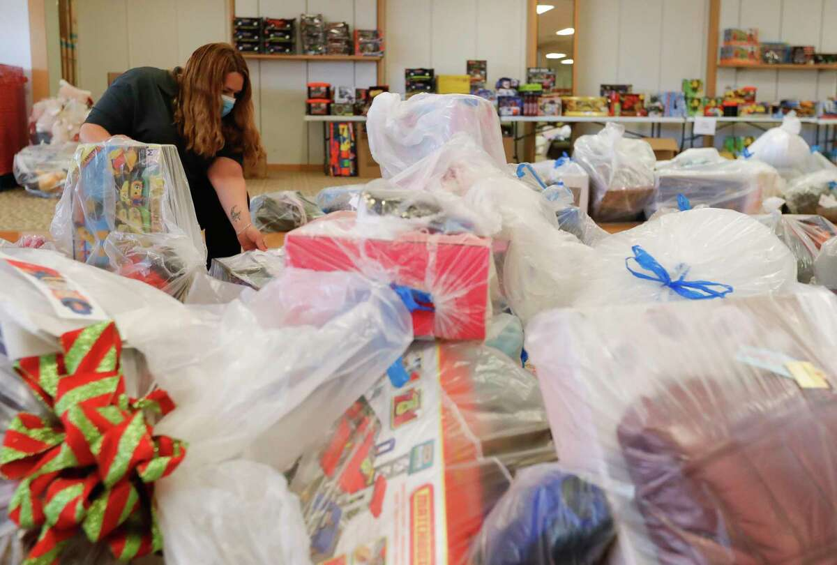 Dolores Tull helps sort through bags of toys for Salvation Army's annual angel tree gift assistance program at the Conroe Outlet Mall, Thursday, Dec. 3, 2020, in Conroe. The Salvation Army is partnering with Toys for Tots to provide gifs for more than 4,000 children.