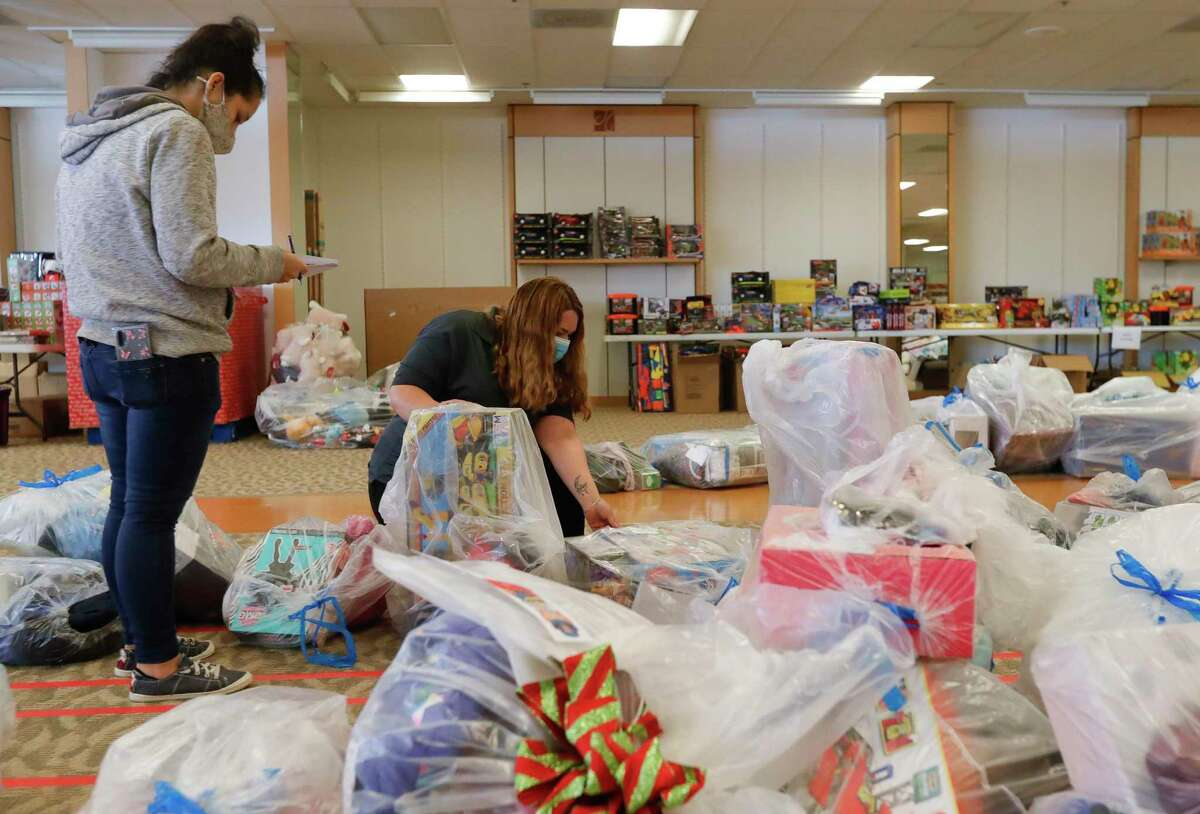 Laura Morales, left, helps Dolores Tull sort through bags of toys for Salvation Army's annual angel tree gift assistance program at the Conroe Outlet Mall, Thursday, Dec. 3, 2020, in Conroe. The Salvation Army is partnering with Toys for Tots to provide gifs for more than 4,000 children.