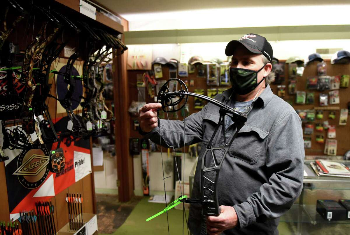 Mick McGuinness, owner of Brown's Archery Shop, shows the mechanics of a modern compound bow on Tuesday, Dec. 8, 2020, at his store in Schenectady, N.Y. McGuiness has seen a jump in business reflecting the increased demand for state hunting licenses. (Will Waldron/Times Union)