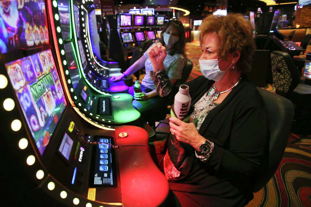 Bibi Cates, 70, of Mountain Home, Texas, reacts as she plays the slot machines at the Lucky Eagle Casino in the Kickapoo Reservation, Wednesday, Sept. 30, 2020. It was the first day of the casino's reopening after closing on March 19 due to the COVID-19 pandemic. The casino opened its first day for VIP invitees. In back is her daughter, Angela Cates, 50.